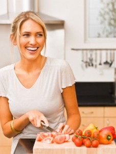 Woman in kitchen chopping fruit