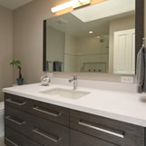 Contemporary Hall Bath Remodel featuring custom cabinetry in Rift White Oak Wood Veneer with medium stain, white quartz countertop, and linear lighting.