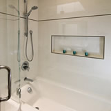 Contemporary Hall Bath Remodel featuring white tile, niche, metal liner and stainless steel fixtures.