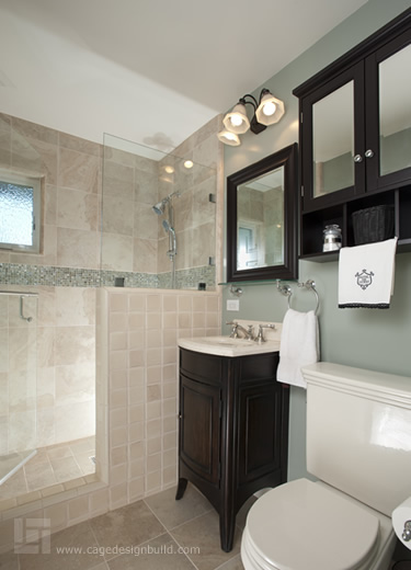 Remodeled hall bathroom features beautiful soft green paint, a radius sink vanity and an oversized tile shower with glass door.