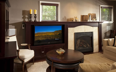 Remodeled family room in San Jose features a redesigned fireplace and built-in TV enclosure.
