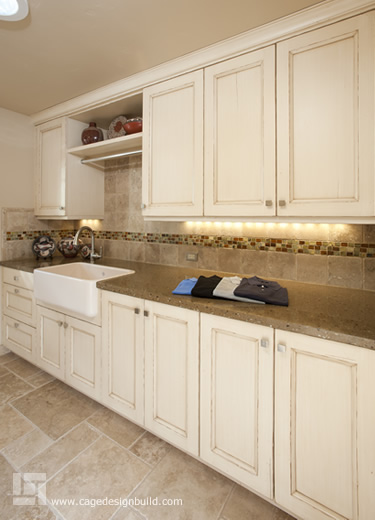 Laundry room with custom concrete countertop from Boheium Stoneworks, Cottonwood Fine Cabinetry, and stone tile with glass tile accents