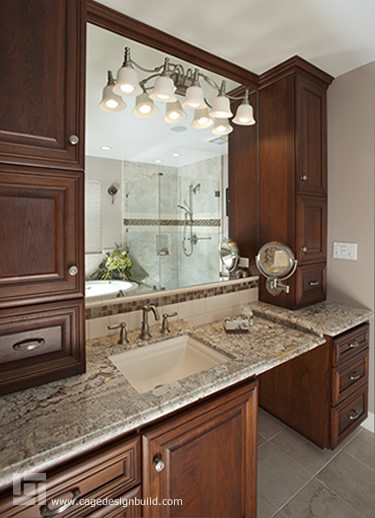 Master bath remodel features a Jacuzzi tub and long counter with vanity area which include a his & her magnified vanity mirror