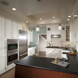 Kitchen remodel featuring bench seating, pendant lighting, Subzero refrigerator and white custom cabinetry.