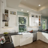 Kitchen remodel with honed absolute black granite, Pella double hung windows, farm house sink and display cabinetry.