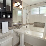 Remodeled upstairs bathroom features tile wainscoting and tub/shower walls with built in soap niche.